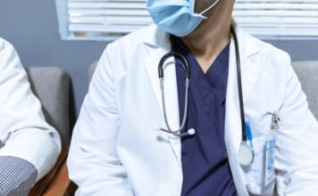 medicine profesional wearing a scrub and a white coat sit at a medical office