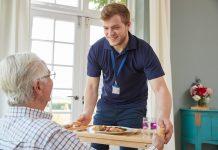 care provider serving breakfast to elderly
